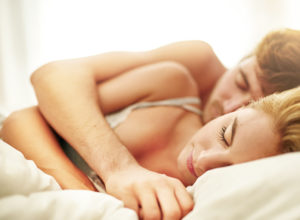 Shot of a young couple asleep in bed at home